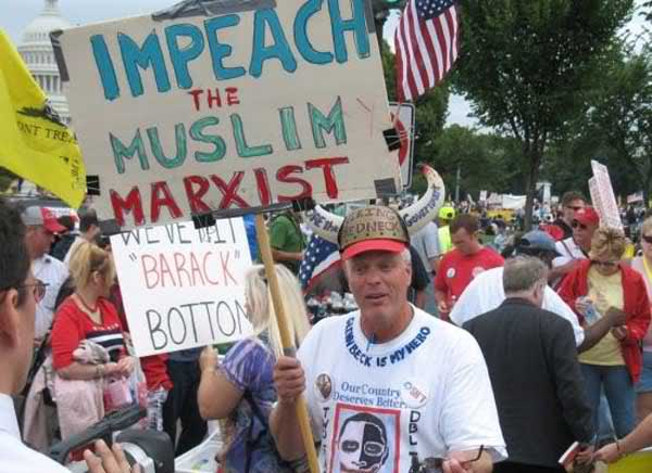 """Unnamed protester at the Taxpayer March on Washington (September 12, 2009). It shows a man, standing among a crowd of protesters near the capitol building in Washington D.C., holding a sign that says """"IMPEACH THE MUSLIM MARXIST"""" and around the collar of his T-shirt is written """"GLENN BECK IS MY HERO."""""""