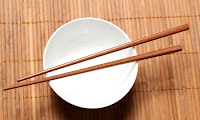 wooden chopsticks resting on a while bowl against a bamboo background 