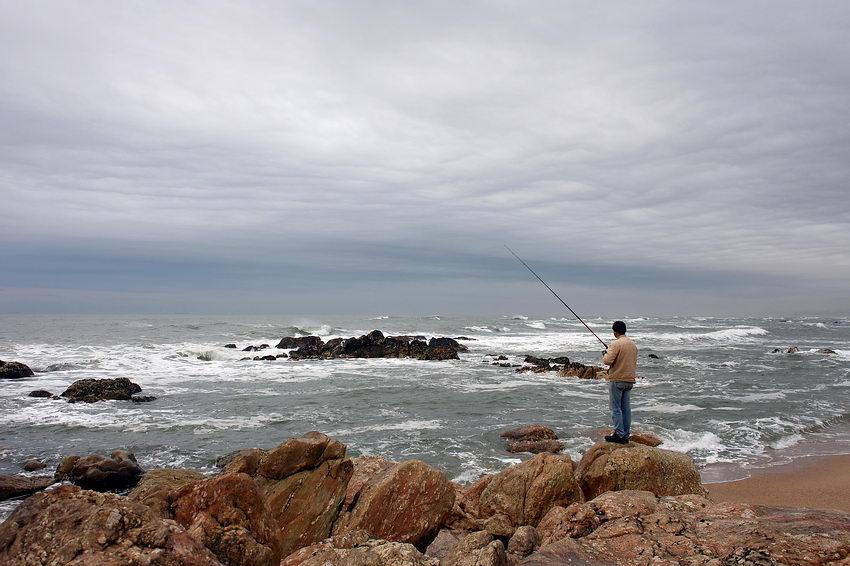 Vista sobre o mar, a partir dos rochedos, nos quais, um pescador de pé com a cana em riste