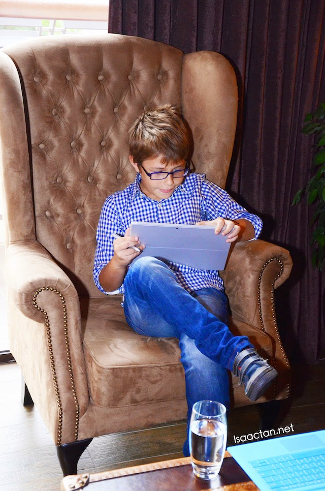 Bruce's son, on his Microsoft device on the sofa while the parents are in the kitchen.