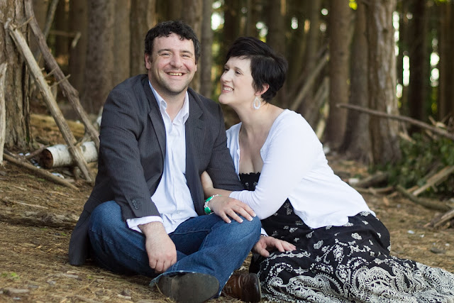 husband and wife sitting in the woods