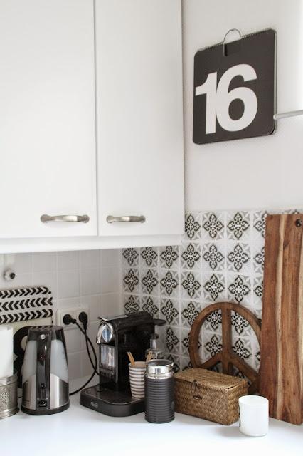 Weiße Küchenfront mit weißer Arbeitsplatte und diversen Küchengeräten in schwarz und holzfarben