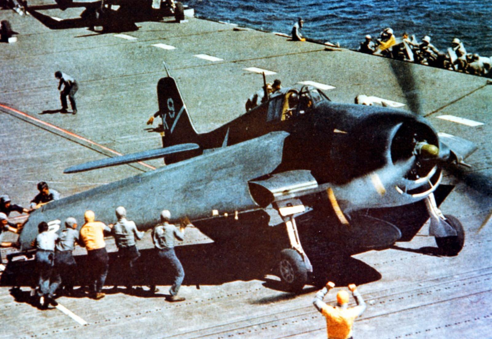 Deck crew of uss yorktown extending the wing of a hellcat fighter