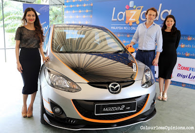 "Mr. Pezelli along with the Lazada brand ambassador posing with the Mazda 2 Hatchback – the Grand Prize for the Lazada ""Giveaway Extravaganza"" contest"
