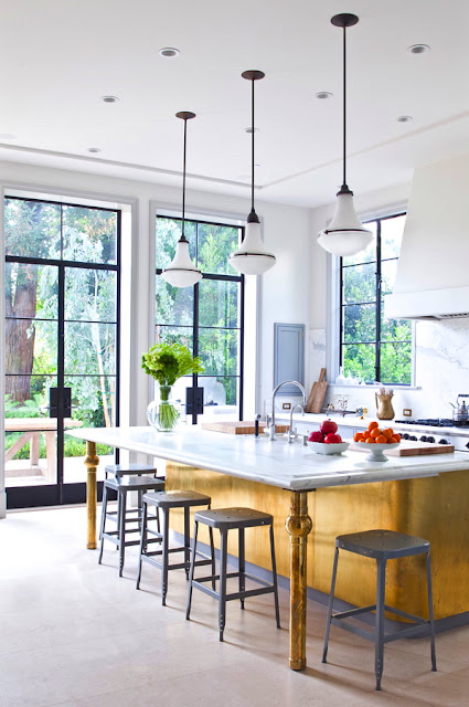 kitchen designed by William Hefner with glass doors, gray stools and yellow island with white marble countertop