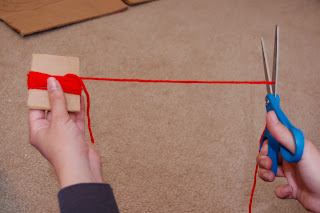 cut yarn on cardboard for pom pom