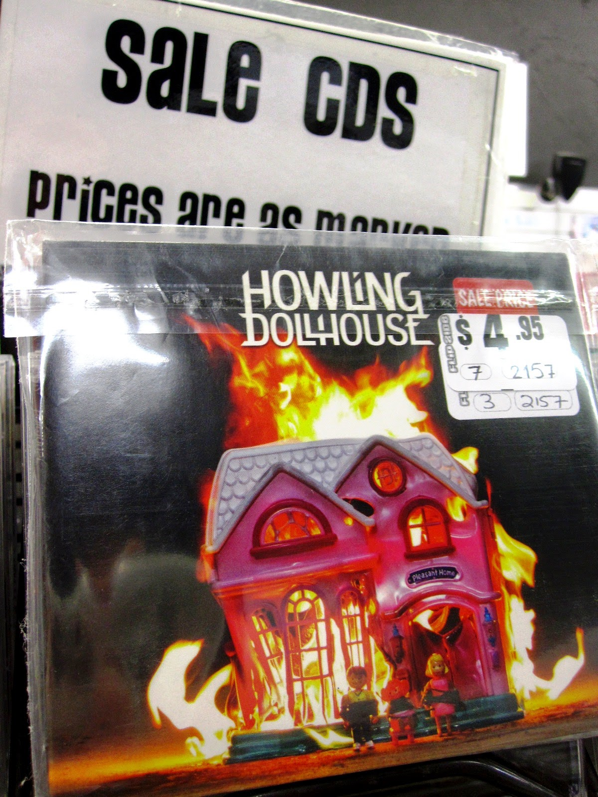CD by the band Howling Dollhouse with a picture of a burning Fisher Price dollhouse on the front cover, in the sale bin.