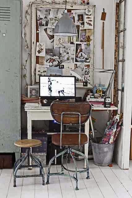 Taboret na metalowych nogach, drewniane krzesło na metalowych nogach, ocynkowane wiadro z rulonami papierów, metalowa szafa, białe biurko