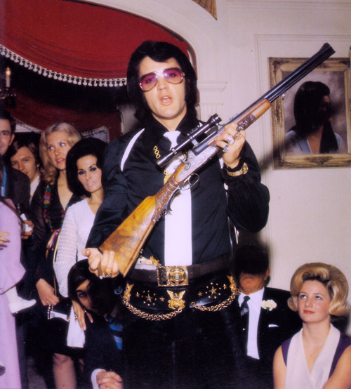 Elvis at home holding a rifle