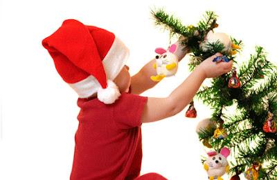 Lindo niño jugando con el arbol de navidad