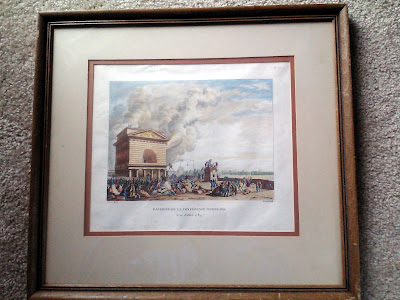 A cheaply framed colored 18th century engraving of a building on fire