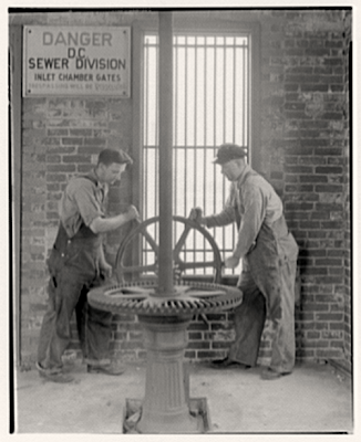Men turning gear wheel