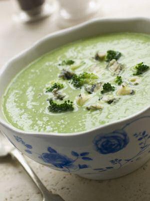 Een kom broccoli kaassoep met Stilton kaas door de soep gesmolten en geserveerd met enkele broccoliroosjes