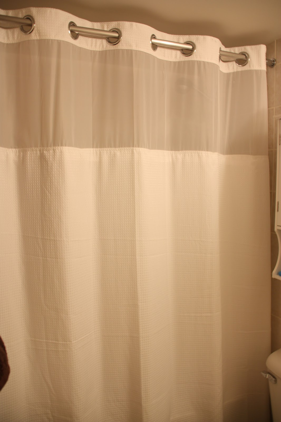 The Curtain Outer Layer Falls On Outside Of Bath Tub And It Has A Second Liner That Inside Is Snapped Onto