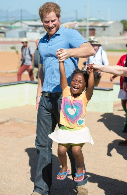 People's prince ... Prince Harry lifts up four-year-old Sinentlantla Jacobs during a visit to South Africa. Picture: WireImageSource:Supplied