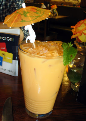 A Glass of Thai iced tea with cute umbrella and mint leaf