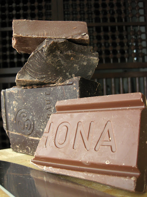 Bulk Callebaut dark chocolate and Valrhona chocolate stacked on top of each other