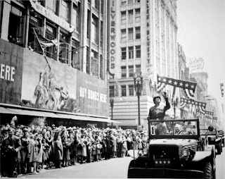 black and white image of World War II returning heroes being welcomed home in a parade.
