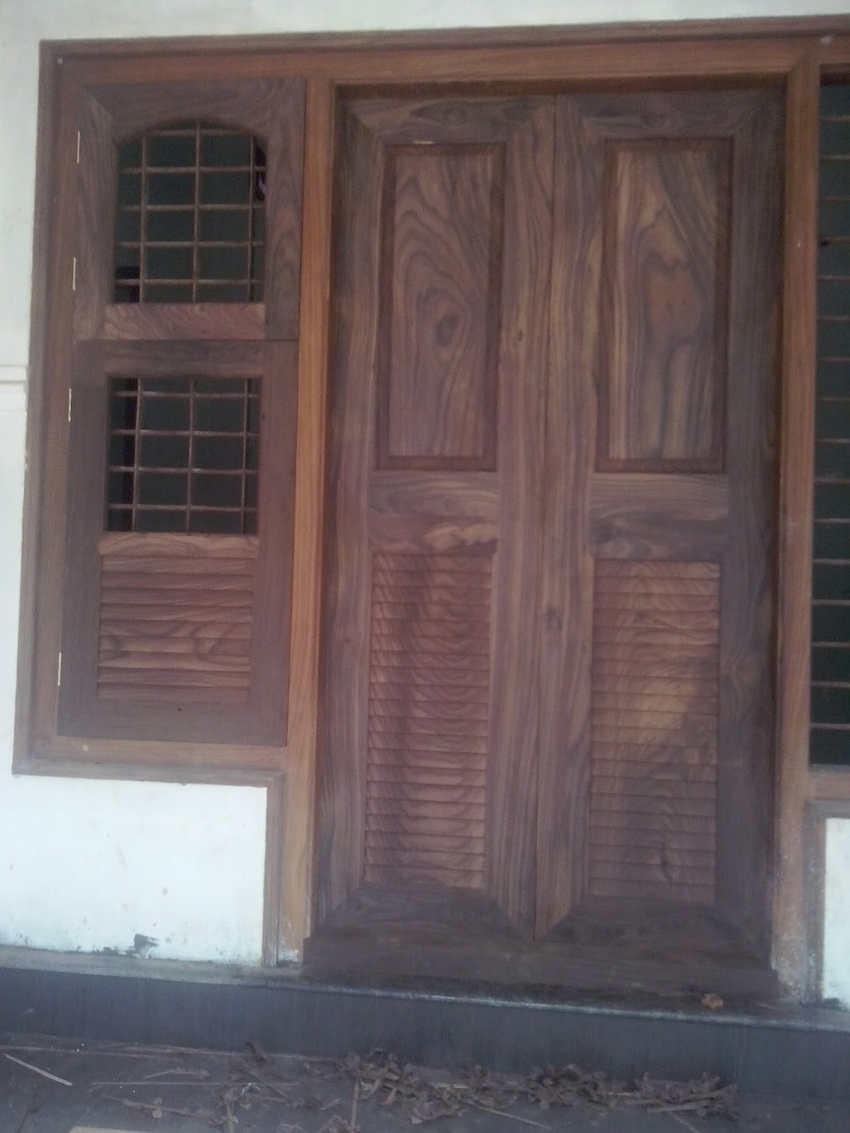 Kerala style carpenter works and designs kerala style for Simple wooden front door designs
