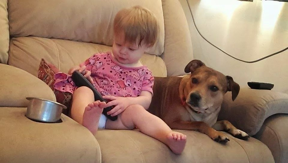 Image: my toddler granddaughter, and my Staffie bull terrier, sitting together on the couch.