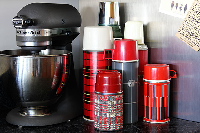 Collection of vintage thermoses used as kitchen decor