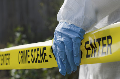 image of crime scene tape and investigator's hand in front of it.