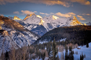 Sunset casts golden light on the mountains of Colorado.  A small cabin is framed by fresh fallen snow.  Durango Colorado