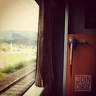 A microphone and a window in a karaoke room on a train in South Korea.