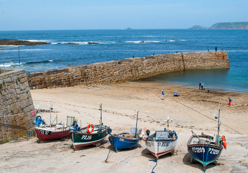 Boats docked on the shore along sennen cove in west cornwall, england, UK