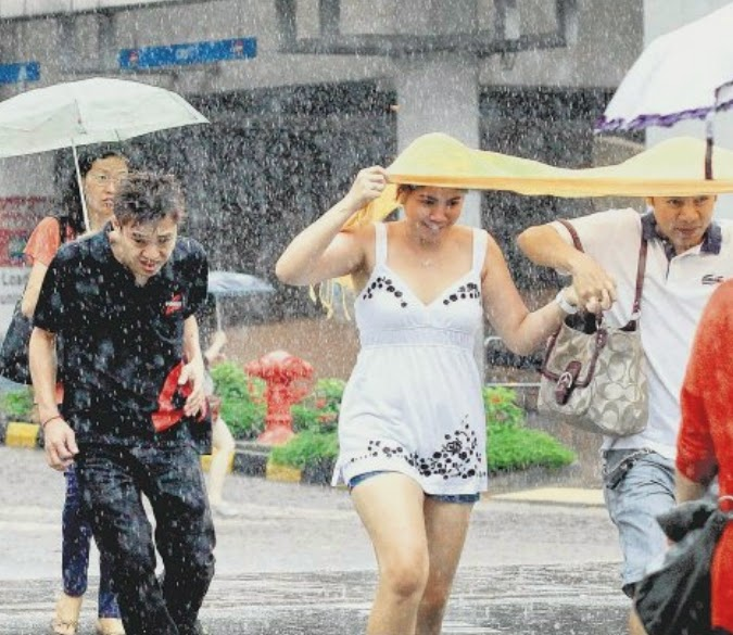 WHAT A JOY! Singaporeans revelling in the heavy rainfall in Victoria Street yesterday after the recent dry spell. The showers were heaviest in the eastern and southern parts of the island.