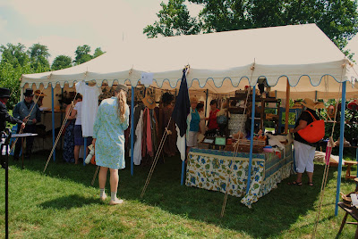 a booth with people shoping for period clothing that they can buy for themselves scarves and dresses hanging on racks under a white tent