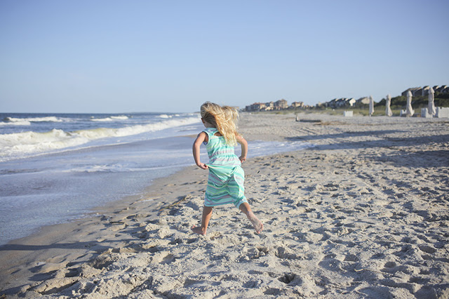 little girl running away from camera on the beach