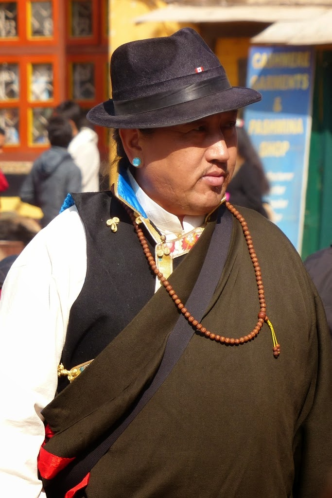 Man in traditional Tibetan dress with a turquoise earring in his ear