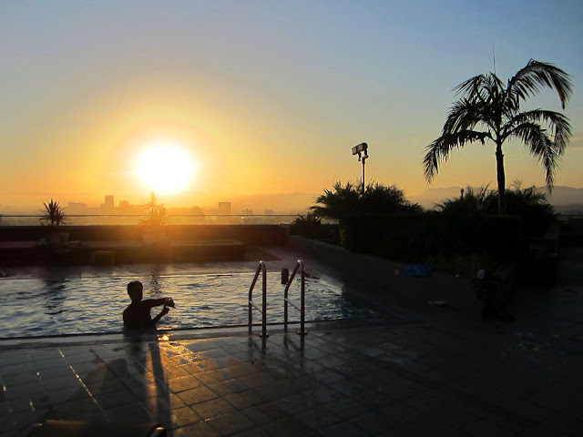 sunset over a pool with a view of Los Angeles