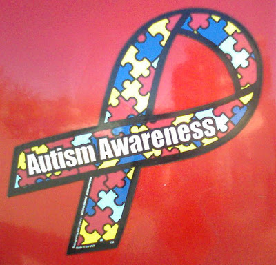 """Autism Awareness"" puzzle-piece ribbon magnet on a car"