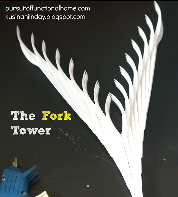 The Fork Tower Project. Blue Hot Glue Gun and white forks on top of the table.