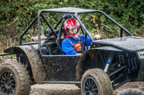 Stag Dressed in Superman outfit driving a Rage Buggy