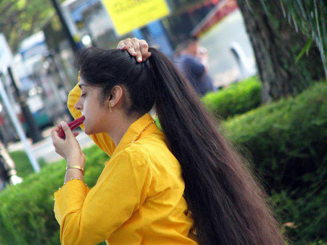 Indian girl styling her hair in veegaland theme park.