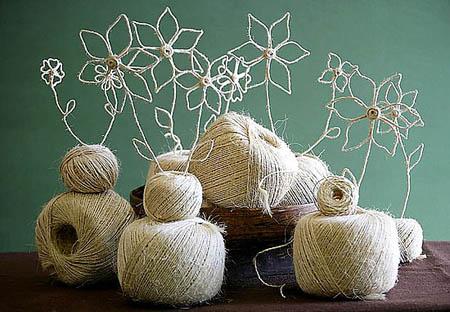 de lana son la base de un centro que lleva flores hechas de la misma