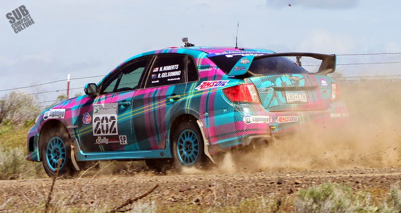 Plaid Subaru WRX STI sedan rally car.