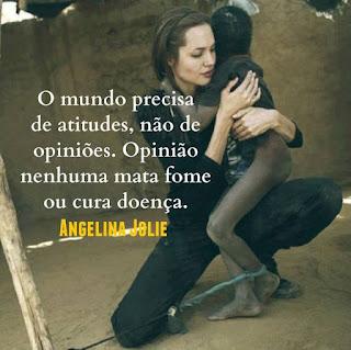 Foto. Angelina Jolie em um pátio de chão de areia, está agachada com o joelho direito apoiado no chão e sobre a coxa da outra perna dobrada e aérea, apoia um garoto magérrimo de pele negra com aspecto ressecado e sujo, o corpo nu parcialmente coberto por camiseta escura, bem maior que ele. Com a cabeça voltada para trás ele abraça a protetora que retribui ternamente espalmando a mão direita abaixo do ombro esquerdo do menino, o braço esquerdo enlaça-o e a mão em concha circunda a frágil cintura. O garoto tem o tornozelo esquerdo amarrado por um tecido azul retorcido, preso a uma corda fortemente estirada em uma estaca de pau. Angelina é uma mulher de pele alva, magra, rosto oval, cabelos castanhos escuros lisos e compridos presos para trás por uma fina tiara preta, sobrancelhas curtas, olhos fechados, nariz médio levemente arrebitado e lábios grossos; ela usa um macacão e botinas pretos. Ao fundo, um muro com reboco rachado e em uma parte à direita, no alto, quebrado. Sobreposto à foto escrito em letras brancas, lê-se: O mundo precisa de atitudes, não de opiniões. Opinião nenhuma mata fome ou cura doença. Angelina Jolie.