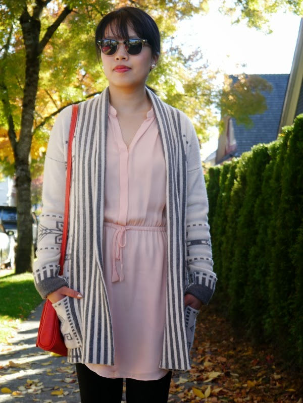 Vancouver blogger Lisa Wong of Solo Lisa wears a grey and ivory Aztec print sweater coat over a blush pink silk tunic and black leggings. She finishes off the outfit with a red leather crossbody bag, shades, black ankle boots, and pearl earrings.