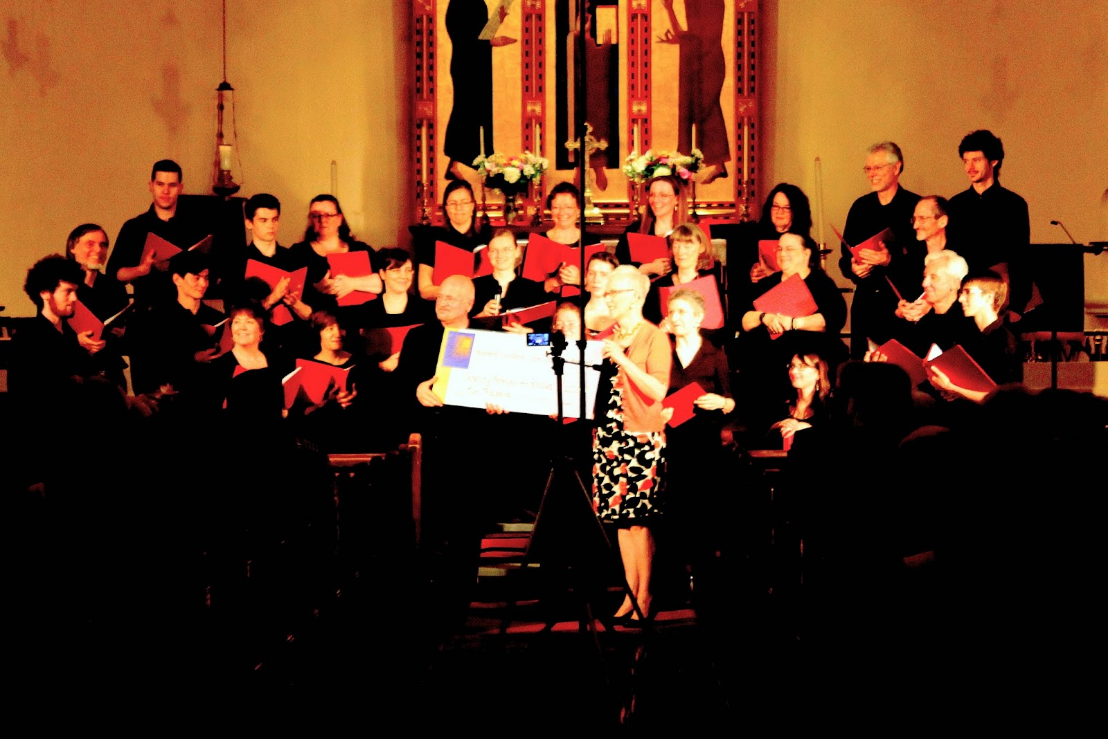 The Stairwell Carollers present a $2000 cheque to a local charity at a 2013 concert