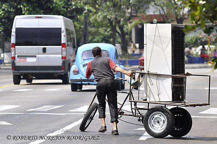 un hombre cargaba un refrigerador en una carretilla