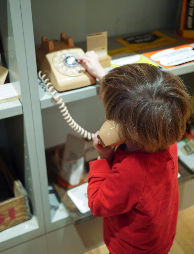 Henry playing with a old fashioned phone in the Pedlars shop in Notting Hill