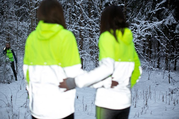 two unknown girls standing with arms on eachother's backs. winter, snow, forest. neon yellow, white, and reflective gray tracksuits, low-res