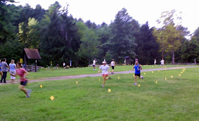 Runners approaching the finish line at the Saratoga Stryders' final 5K trail race, Aug 5 at Camp Saratoga.