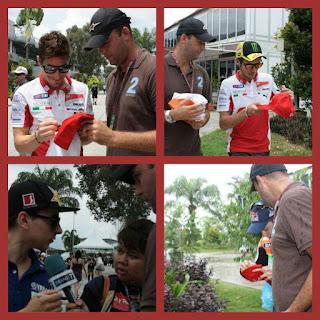los campones de MotoGP firmando gorra para causa solidaria