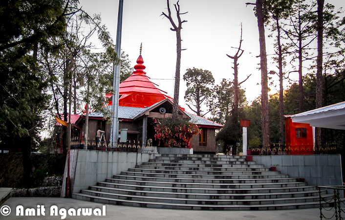 Sankat Mochan Temple is one of the popular Temples in Shimla Town. It's not exactly in Shimla, but quite near to it. Let's have a quick Photo Journey from Sankat Mochan Temple by Amit Agarwal.. Sankat Mochan Temple is actually located near to Tara-Devi which comes on the way to Kalka from Shimla Town. It's approximately 10 kilometers from Shimla Town. Place is surrounded by green mountains all around. Temple is adjacent to the National Highway - 22. The temple is a place where one can actually meditate and enjoy the calm and peaceful surroundings.The very first photograph above shows a temple on left, which is located just after main entry into the Sankat Mochan Temple. This temple is created in South Indian Style.Around 1950, a Baba came to this beautiful place and discovered the perfect spot for meditation and soulful introspection. After staying here for 10 days, he desired that a temple dedicated to Lord Hanuman should be built here. Baba's faithful devotees included the governor of Himachal Pradesh, who along with Bhagvan Sahai took up the task of building the temple and fulfilling their Guru's wish.Sankat Mochan temple has many facilities for people and also includes a three-storey building that is used for many purposes. Every Sunday, the huge hall in the building is used for distributing Prasad, also known as Langar. Langar at Sankat Mochan is quite different and very well managed.  One portion of the building is used to conduct marriage ceremonies and is rented out to people who want to conduct marriages. The temple charges a very nominal fee for this. Apart from marriages, there are many other sacred rituals and ceremonies that can be conducted over here. Priests and the maintenance staff, who work here day and night, use the rest of the building as a residential complex. The temple also has an Ayurvedic clinic...Here is a photograph showing interiors of main Sankat Mochan Temple.There are few small Temples in the campus which are dedicated to different godsSankat Mochan Temple is dedicated mainly to Lord Hanuman, though one finds idols of Lord Rama, Shiva and Ganesha in separate complexes. There is a specially made temple for Baba Neeb Karori Ji Maharaj also. The temple dedicated to Lord Ganesha has been built in the South Indian style of architecture and is worth the visitSankat Mochan Temple is popular temple in Shimla region, which attracts people from all ages and genders who come here to pay obeisance to Lord Hanuman. Sankat Mochan Temple is second most famous temple after Jakhu Temple dedicated to Lord Hanuman. This temple located 5 km away from a beautiful hill station ShimlaOne can have easy transportation to Sankat Mochan Temple from Shimla Bus Stand and other places. From Shimla there are frequent buses till Taradevi and have a stoppage near Sankat Mochan Temple. If you there on Sunday, don't miss the Langar. Langar at Sankat Mochan is quite different and lovableAbove photograph shows the view of Shimla Town from Sankat Mochan Temple.