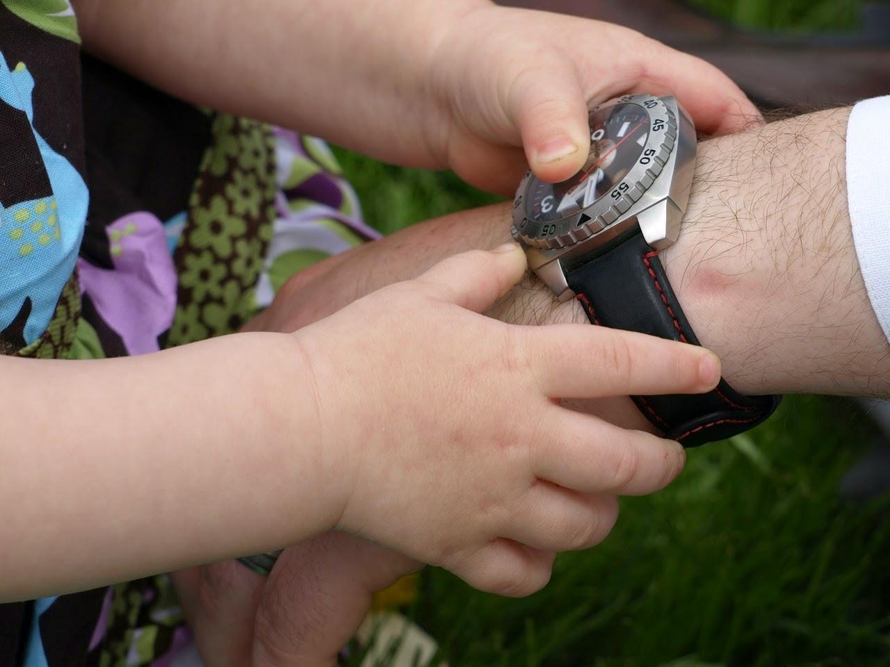 Kind spielt mit Uhr am väterlichen Handgelenk